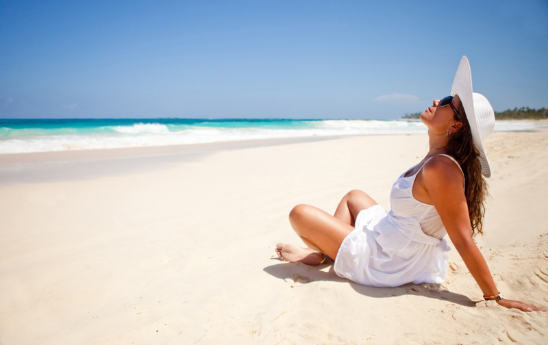 Peaceful woman sitting at the beach enjoying the ocean and relaxing